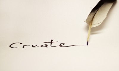 """Inscription """" Create """" written with a feather on a white paper"""