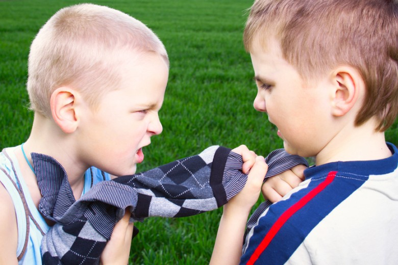 Children fighting over a sweater